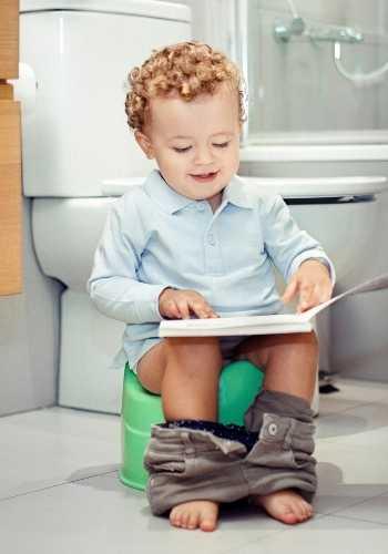 niño sentado en el wc